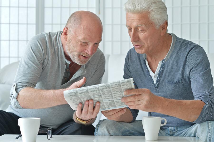 dva muškarca čitaju novine kod kuće